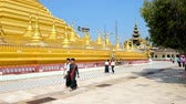 rendilhado : BAGO, MYANMAR - FEBRUARY 15, 2018: The Buddhist devotees walk around the golden stupa of Shwemawdaw Pagoda, on February 15 in Bago. Stock Footage