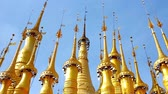 Бирма : Ornate golden hti umbrellas with ringing bells decorate the medieval pagodas of Inn Thein Buddha Image Shrine, located in the same named village on Inle Lake, Myanmar. Стоковые видеозаписи