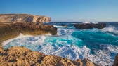 máltai : The rocky coastline of Gozo Island of Maltese Archipelago next to the Azure Window, stormy waves strike the cliffs with white splashes, Malta. Stock mozgókép