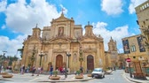 máltai : RABAT, MALTA - JUNE 16, 2018: Square in front of medieval Collegiate church of St Paul is decorated with colorful garlands and lanterns to the Feast of St Peter and St Paul, on June 16 in Rabat. Stock mozgókép