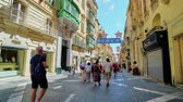 máltai : VALLETTA, MALTA - JUNE 17, 2018: Central city street Triq Ir-Repubblika, decorated due to Film Festival, numerous stores, cafes and bars located in historical medieval mansions, on June 17 in Valletta