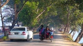 inlay : NYAUNGSHWE, MYANMAR - FEBRUARY 20, 2018: The cars ride along the shady road at Tharzi pond, on February 20 in Nyaungshwe Stock Footage