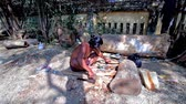 rendilhado : BAGAN, MYANMAR - FEBRUARY 25, 2018: The young artisan carving carves the wooden sculpture in shade of trees at his workshop, located next to the Shwezigon Pagoda market, on February 25 in Bagan.