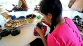 délkelet Ázsia : BAGAN, MYANMAR - FEBRUARY 25, 2018: The young artisan demonstrates the art of eggshell inlay, decorating the small lacquer tea bowl in traditional lacquerware workshop, on February 25 in Bagan Stock mozgókép