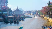 inlay : NYAUNGSHWE, MYANMAR - FEBRUARY 20, 2018: Busy harbor of village with numerous tourist and fishermens canoes, residential houses and Buddhist Temple on the canal banks, on February 20 in Nyaungshwe