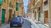 john : VALLETTA, MALTA - JUNE 17, 2018: Walk along the narrow St Paul street with preserved medieval churches, mansions with colored wooden Maltese balconies and many parked cars, on June 17 in Valletta.