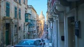 máltai : VALLETTA, MALTA - JUNE 17, 2018: The walk along the narrow Old Mint street with descents and climbs with a view on giant dome of Carmelite Church and historical mansions, on June 17 in Valletta.