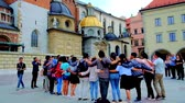 krakow : KRAKOW, POLAND - JUNE 10, 2018: The group of tourists, hugging in circle, sing religious songs in courtyard of Wawel Castle next to the Chapels of Cathedral, on June 10 in Krakow.