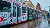 все : KRAKOW, POLAND - JUNE 13, 2018: The trams ride along the All Saints Square with a view on Holy Trinity Basilica on wet rainy weather, on June 13 in Krakow.