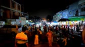 dagon : YANGON, MYANMAR - FEBRUARY 27, 2018: The crowded night market at the Eastern Gate of Shwedagon Pagoda, people choose the street food, gifts and religious goods, on February 27 in Yangon. Stock Footage