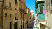 konak : VALLETTA, MALTA - JUNE 17, 2018: The hilly Old Mint street with tall residential edifices and a view on huge dome of Carmelite Church, on June 17 in Valletta. Stok Video