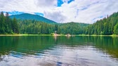 vor : The picturesque Synevyr Lake is surrounded by coniferous forests and Carpathian mountains, the clear surface reflects fast flowing clouds, the tourists enjoy the trip on wooden rafts, Ukraine.