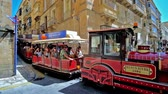 sestup : VALLETTA, MALTA - JUNE 17, 2018: The Malta Fun Train entertain the tourists, riding in narrow city streets among historical mansions, small cafes and old churches, on June 17 in Valletta Dostupné videozáznamy
