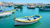 máltai : MARSAXLOKK, MALTA - JUNE 18, 2018: The scenic fishing village with old luzzu boats in harbour, family cafes and souvenir stalls on promenade, on June 18 in Marsaxlokk.