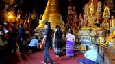 Бирма : PINDAYA, MYANMAR - FEBRUARY 19, 2018:  Interior of Pindaya cave Buddhist site with numerous pilgrims in front of the spectacular golden images of Lord Buddha and small stupa, on February 19 in Pindaya