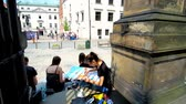 dik dik bakmak : KRAKOW, POLAND - JUNE 11, 2018: The students of Art Academy create the sketches and paintings of architectural forms, sitting in shade of the stone fence in Godzka street, on June 11 in Krakow. Stok Video