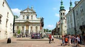 krakow : KRAKOW, POLAND - JUNE 11, 2018: The tourist groups cross St Mary Magdalene Square with a view on St Peter and Paul Church and the Church of St Andrew with tall belfries, on June 11 in Krakow.