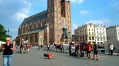krakow : KRAKOW, POLAND - JUNE 11, 2018: The street dancers entertain people in Main Market square with  a view on riding horse carriages and St Mary Basilica on background, on June 11 in Krakow. Stock Footage