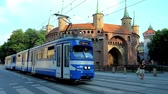 fellegvár : KRAKOW, POLAND - JUNE 11, 2018: The  vintage tram rides along the Basztowa street with a view on Barbikan fortified outpost and St Florian Gate (Brama Florianska) on background, on June 11 in Krakow.
