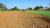 Бирма : The plowed soil on the field and the farmer, working with tiller on background, Hum Pho, Taunggyi, Myanmar.