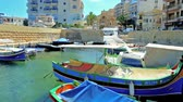 máltai : BUGIBBA, MALTA - JUNE 14, 2018: The colorful wooden luzzu boats in fishing harbor with a view on St Pauls Shipwreck Church on the background, on June 14 in Bugibba.