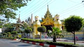 dagon : YANGON, MYANMAR - FEBRUARY 17, 2018: The North Gate of Shwedagon Pagoda with two huge leogryphs (chinthe) guardians and ornate spire above the covered gallery, on February 17 in Yangon. Stock Footage