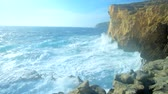 máltai : The strong Mediterranean foaming waves smash against the massive rock on Azure Window coast, spreading clouds of hazy spay, San Lawrenz, Gozo Island, Malta.