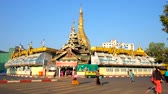 yangon : YANGON, MYANMAR - FEBRUARY 17, 2018:  Pedestrians cross the wide Maha Bandula road in front of historic Sule Pagoda, its main stupa is seen behind the market stalls, on February 17 in Yangon.