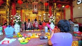 yangon : YANGON, MYANMAR - FEBRUARY 17, 2018: The woman with incense sticks prays at the altar of Kheng Hock Keong Temple with fruit and flower offerings, on February 17 in Yangon.
