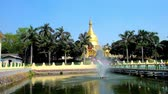 dagon : The fountain in pond of Maha Wizaya (Mahavijaya) Pagoda, surrounded by lush greenery, hiding the huge golden stupa, Yangon, Myanmar.
