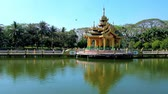 yangon : The scenic Buddhist shrine with carved pyatthat roof is reflected in pond of Theingottara park, Yangon, Myanmar. Stock Footage