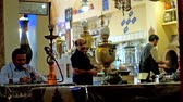 sofra takımı : TEHRAN, IRAN - OCTOBER 25, 2017: Hall of traditional Azari Chaykhaneh (teahouse) with local man, smoking shisha and a view on samovars with tea pots on the background, on October 25 in Tehran. Stok Video