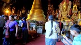 oração : PINDAYA, MYANMAR - FEBRUARY 19, 2018: The scenic golden images of Lord Buddha and small stupa in Pindaya cave - the famous Buddhist complex, on February 19 in Pindaya