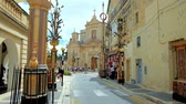 máltai : RABAT, MALTA - JUNE 16, 2018: The view on Collegiate St Pauls Church from St Agatha street, decorated with large flower garlands due to the city feast, on June 16 in Rabat. Stock mozgókép