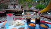 cena urbana : The tourists feed domestic geese in outdoor restaurant on Darband river, while their own dinner with tasty dizi abgusht (lamb stew in pot) is getting cold on the trestle bed, Tehran, Iran. Stock Footage