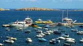 máltai : BUGIBBA, MALTA - JUNE 14, 2018: The pleasure boats offer the tourist trips along the St Pauls Bay from the fishing harbour of resort, on June 14 in Bugibba.