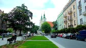 krakow : KRAKOW, POLAND - JUNE 12, 2018: Jan Matejko square is occupied with scenic park, St Florians square with tall bell towers is seen on the background, on June 12 in Krakow