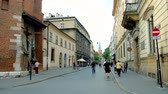 krakow : KRAKOW, POLAND - JUNE 12, 2018: Walk along Slawkowska street with a view on the Holy Cross on wall of the church of St Mark the Evangelist, on June 12 in Krakow. Stock Footage