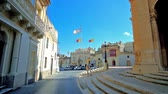 keskeny : SIGGIEWI, MALTA - JUNE 16, 2018: San Nikola street of old town with a view on historic mansions with flags in square in front of St Nicholas Parish Church, on June 16 in Siggiewi.