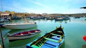 máltai : MARSAXLOKK, MALTA - JUNE 18, 2018: The fishing boats in Marsaxlokk Bay harbour with historic buildings of the village on the background, on June 18 in Marsaxlokk.