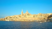 konak : Enjoy the yacht trip along the medieval city walls of Valletta with a view on scenic bell tower of St Pauls Anglican Pro-Cathedral and the dome of Carmelite Church, Malta. Stok Video
