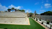 держать : The fast running clouds above the St Peters Bastion of Mdina citadel, surrounded by ornamental garden, stretching along the deep moat, Malta. Стоковые видеозаписи