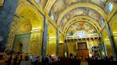 фреска : VALLETTA, MALTA - JUNE 18, 2018: Panorama of stunning interior of St Johns Co-Cathedral with carved gilt patterns, frescoes, sculptures, scenic altar and apse, on June 18 in Valletta. Стоковые видеозаписи