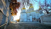 monge : KIEV, UKRAINE - OCTOBER 19, 2018: The ascent along the way at ramparts of Kiev Pechersk Lavra monastery with a view on apse of Dormition Cathedral and setting sun, on October 19 in Kiev.