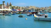 造船所 : MARSAXLOKK, MALTA - JUNE 18, 2018: The picturesque fishing village is one of the most popular tourist places, attracting with traditional luzzu boats in harbour, on June 18 in Marsaxlokk.
