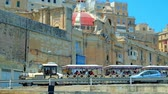bastião : VALLETTA, MALTA - JUNE 19, 2018: The tourist train, driving along Quarry Wharf with a view on city fortifications, old housing and Church of Our Lady of Liesse, on June 19 in Valletta