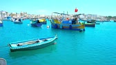 estaleiro : MARSAXLOKK, MALTA - JUNE 18, 2018: Enjoy the peaceful atmosphere in tourist and fishing village, watching traditional luzzu boats, bobbing on calm waters of the harbour, on June 18 in Marsaxlokk
