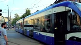 yahudi : KRAKOW, POLAND - JUNE 21, 2018: The modern trams drives along the busy Jozef Dietl avenue, lined with old edifices, on June 21 in Krakow. Stok Video