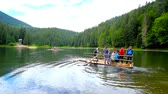 karpaty : SYNEVYR, UKRAINE - JULY 1, 2018: Tourists make the raft trip to Sea Eye Island in beautiful Synevyr Lake, on July 1 in Synevyr.