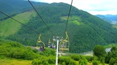 karpaty : MIZHHIRIA, UKRAINE - JULY 1, 2018: Enjoy the views from the chair of ski lift of Makovytsia Mount, it overlooks fantastic landscapes of Carpathians and curved mountain rivers, on July 1 in Mizhhiria.